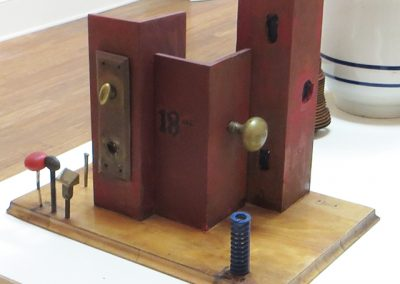 """Fred Cole  – """"18 East"""" recycled metal door components, wood, plastic"""