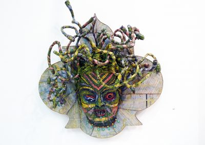 Wall Street Medusa – relief sculpture on panel with paper mache', wire, Wall Street Journal, gauze and oil paint, snake skin and plastic jewels – 22″ x 19″ x 6″