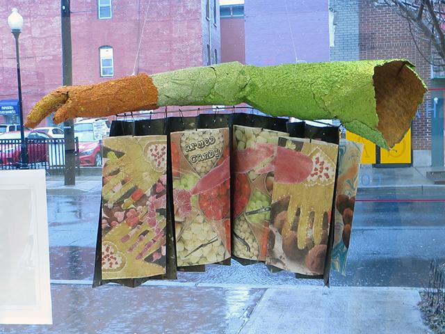 "Pat Feeney-Murrell ""Armed Candy"" flax handmade paper arm, digital transfer, candy and gum imprints onaccordion flag book on rod, $1,500.00"
