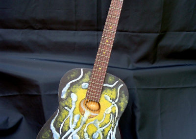 The Birth of Folk – found guitar, hot glue, wooden egg, reflective vinyl, paint