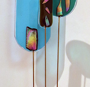 """Three for One""   fused glass, brass rods and wood, by Ellen Rebarber"