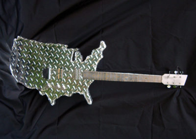 American Prototype – laminated wood cut to USA shape, faux diamond plate, electric guitar parts, hand polished metal fret board with hand set frets, paint – owned by collector